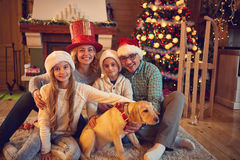 Family and dog sitting by xmas tree. Smiling family and dog sitting by xmas tree Royalty Free Stock Photo