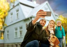 Family with dog taking selfie over house in autumn. Family, pets and people concept - happy mother, father and little daughter with beagle dog taking selfie by stock images