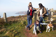 Family With Dog Walking Along Coastal Path Stock Image