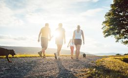 Family and dog walking home. In a rural setting Royalty Free Stock Photos