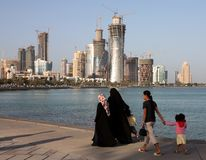 Family on Doha Corniche. Covered Qatari women with their children and housemaid strolling on the Corniche in Doha, Spring 2008, with the New District Royalty Free Stock Images