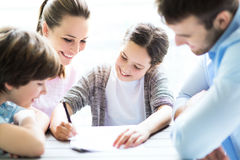 Family doing homework together at table Royalty Free Stock Photos
