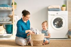 Family doing laundry. Beautiful young women and child girl little helper are having fun and smiling while doing laundry at home stock photo