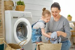 Family doing laundry. Beautiful young women and child girl little helper are having fun and smiling while doing laundry at home royalty free stock photos