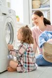 Family doing laundry. Beautiful young women and child girl little helper are having fun and smiling while doing laundry at home royalty free stock photo