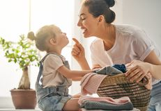 Family doing laundry at home. Beautiful young women and child girl little helper are having fun and smiling while doing laundry at home Royalty Free Stock Images