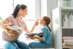 Family doing laundry at home. Beautiful young women and child girl little helper are having fun and smiling while doing laundry at home royalty free stock photos