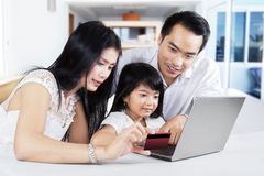 Family doing online shopping at home. Modern family using a laptop computer and credit card to online shopping at home Stock Images