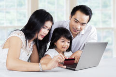 Family doing purchasing online at home. Happy family doing online payment by using a credit card and laptop computer at home Royalty Free Stock Photos