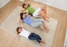 Family Doing Situps On Rug At Home Stock Image
