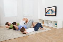 Family doing situps while watching tv Royalty Free Stock Photos