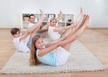 Family doing stretching exercises Stock Photo