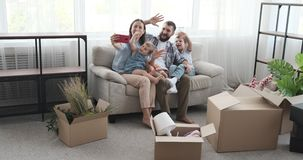 Family doing video call using mobile phone in new home stock video footage