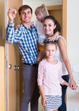 Family at doorway of rented property. Happy parents with kids standing at doorway of rented property royalty free stock photography