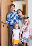Family at doorway of rented property. Happy smiling parents with kids standing at doorway of rented property stock photos
