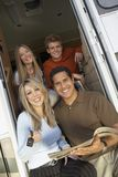 Family At The Doorway Of RV. Portrait of happy couples sitting at the doorway of RV royalty free stock photography