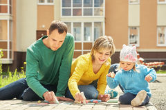 Family draw chalk on asphalt. Parents with a child draw chalk on asphalt. outdoor playing family. Mom, dad and kid Royalty Free Stock Photos