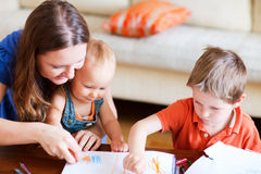 Family drawing. Young mother and her two kids drawing together. Can be used also in kindergarten/daycare context stock image