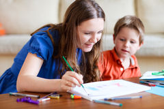 Family drawing. Young mother and her two kids drawing together. Can be used also in kindergarten/daycare context royalty free stock photography