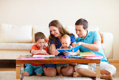 Family drawing and reading. Young happy family with two kids drawing and reading together Stock Images