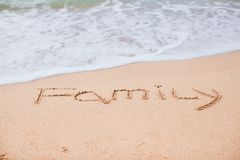 Family drawing in the sand on a tropical beach Stock Photo
