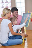 Family drawing on school board at home. Happy young family teach leassons and prepare their son for school while draw on board at home Stock Images