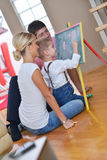 Family drawing on school board at home. Happy young family teach leassons and prepare their son for school while draw on board at home Stock Photography