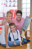 Family drawing on school board at home. Happy young family teach leassons and prepare their son for school while draw on board at home Stock Image