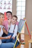 Family drawing on school board at home. Happy young family teach leassons and prepare their son for school while draw on board at home Royalty Free Stock Photo