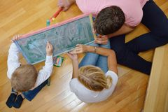 Family drawing on school board at home. Happy young family teach leassons and prepare their son for school while draw on board at home Stock Photo