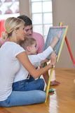 Family drawing on school board at home. Happy young family teach leassons and prepare their son for school while draw on board at home Stock Photos