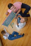 Family drawing on school board at home. Happy young family teach leassons and prepare their son for school while draw on board at home Royalty Free Stock Photos