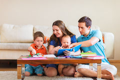 Family drawing. Young family with two kids drawing and reading together stock image