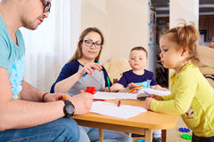 The family draws pencils at a table in room Stock Photo