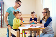 The family draws pencils at a table in room.  Royalty Free Stock Images