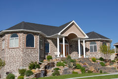 Family Dream Home. 350,000 family home made of brick,  with a blue sky and landscape yard Stock Image