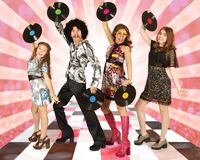 Family dressed in disco style with vinyl records. Dancing on a colored background stock photography