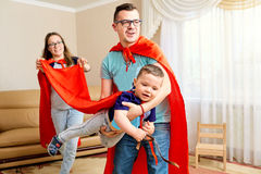 A family dressed in superhero costumes plays  the room Stock Photography