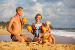 Family drink cocnut at the beach at sunset.  Royalty Free Stock Image