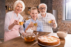 Family drinking tea at home. Grandparents and girl drinking tea with pie together at home Royalty Free Stock Photo