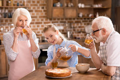 Family drinking tea at home. Grandparents and girl drinking tea with pie together at home Royalty Free Stock Photography