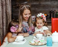 Family drinking tea woman mother daughter posing kitchen plates home made cups tea sisters royalty free stock photography