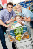 Family drives cart with food and son sitting there. With watermelon. Concept of fresh and healthy food and consumerism royalty free stock photo