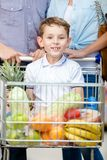 Family drives shopping trolley with food and boy who sits there Stock Photos