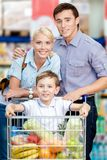 Family drives shopping trolley with food and son sitting there. Concept of fresh and healthy food and consumerism Stock Photography