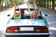 Family driving along in a sports car. Having fun stock image