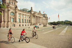Family driving by cycles around Reichstag building Stock Photos