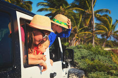 Family driving off-road car on tropical beach Stock Photos