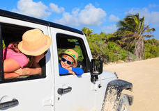 Family driving off-road car on tropical beach Stock Image