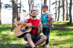 Family duet: Dad playing the guitar with his daughter, free space for your text. Dad& x27;s day, outdoor recreation stock photos